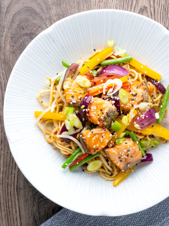 Overhead salmon stir fry with egg noodles and vegetables.