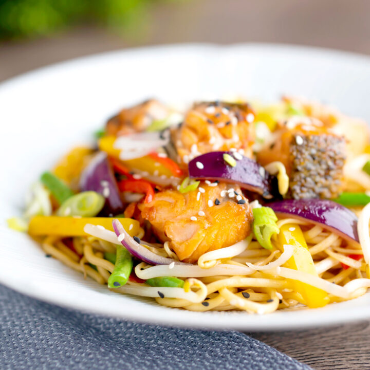 Spicy salmon stir fry with egg noodles and vegetables in a white bowl.