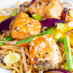 Close up salmon stir fry with egg noodles and vegetables featuring a title overlay.