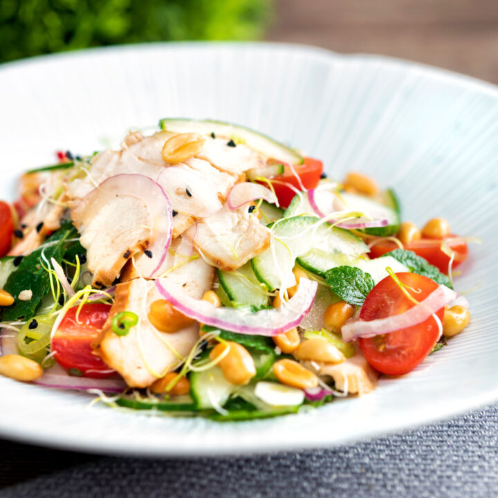 Crunchy & spicy Thai chicken salad with peanuts cucumber & tomatoes.