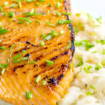 Honey mustard salmon fillet served on celeriac mash with snipped chives featuring a title overlay.