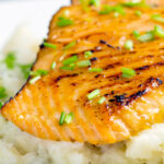 Close up pan fried honey mustard salmon served on celeriac mash featuring a title overlay.