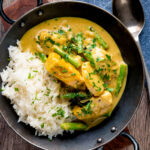 Keralan fish curry with coconut milk featuring green beans and potato with a title overlay.