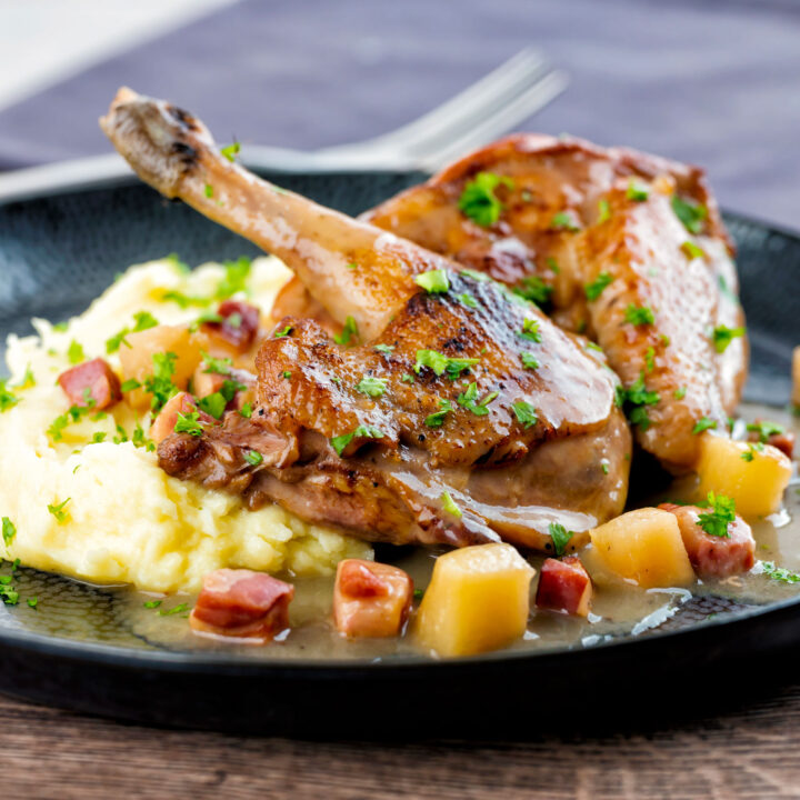 Pheasant casserole with a cider gravy, bacon & apples served on a black plate with mash.