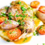 Rabbit Cacciatore or Coniglio alla Cacciatora with shallot and cherry tomatoes on polenta featuring a title overlay.