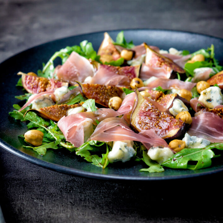 Roasted figs in a salad with prosciutto ham, rocket, blue cheese and hazelnuts.