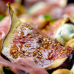 Close up roasted figs served in a salad featuring a title overlay.