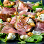 Roasted figs with prosciutto ham, rocket, blue cheese and hazelnuts featuring a title overlay.