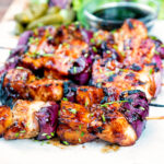 BBQ chicken skewers with pineapple and red onion with a sweet and sour glaze featuring a title overlay.