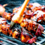 BBQ chicken skewers with pineapple & red onion cooking on a barbecue featuring a title overlay.