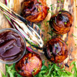 Overhead stuffed onions wrapped in bacon & BBQ sauce glaze featuring a title overlay.