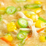 Close up Chinese style chicken and sweetcorn soup with spring onion featuring a title overlay.