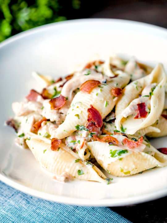 Creamy chicken and bacon pasta served in a white bowl.