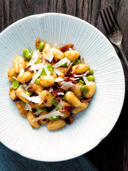 Overhead pan fried gnocchi with bacon, broad beans and parmesan shavings.
