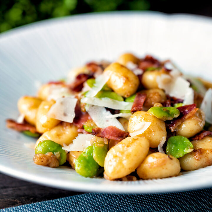Pan fried gnocchi with bacon, broad beans and parmesan shavings served in a white bowl.