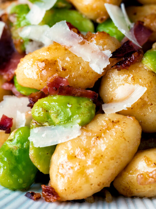 Close up pan fried gnocchi with bacon, broad beans and parmesan shavings.