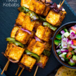 Overhead paneer tikka skewers served with kachumber salad and naan bread featuring a title overlay.