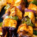Close up paneer tikka skewers featuring a title overlay.