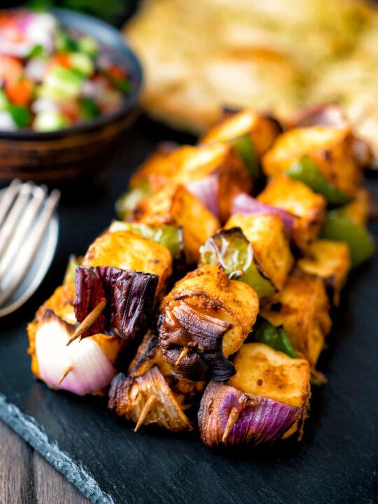 Paneer tikka kebab skewers served with kachumber salad and naan bread.