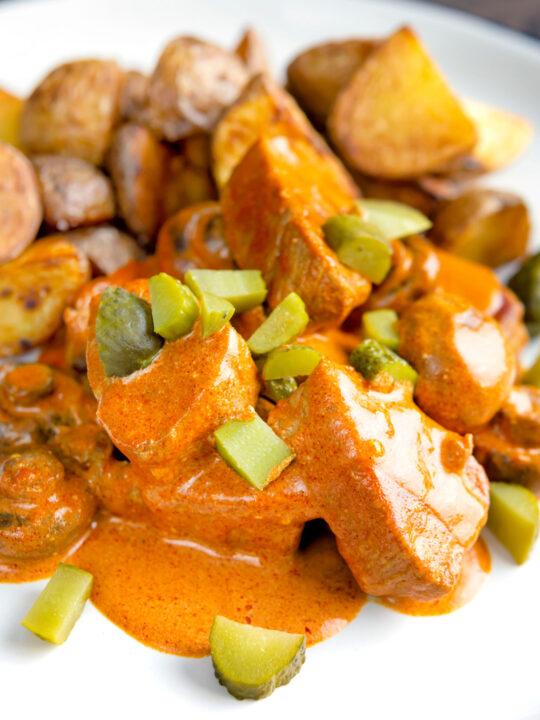 Close up pork tenderloin stroganoff with mushrooms and fried potatoes.