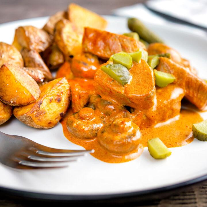 Pork tenderloin stroganoff with mushrooms, fried potatoes and pickles.