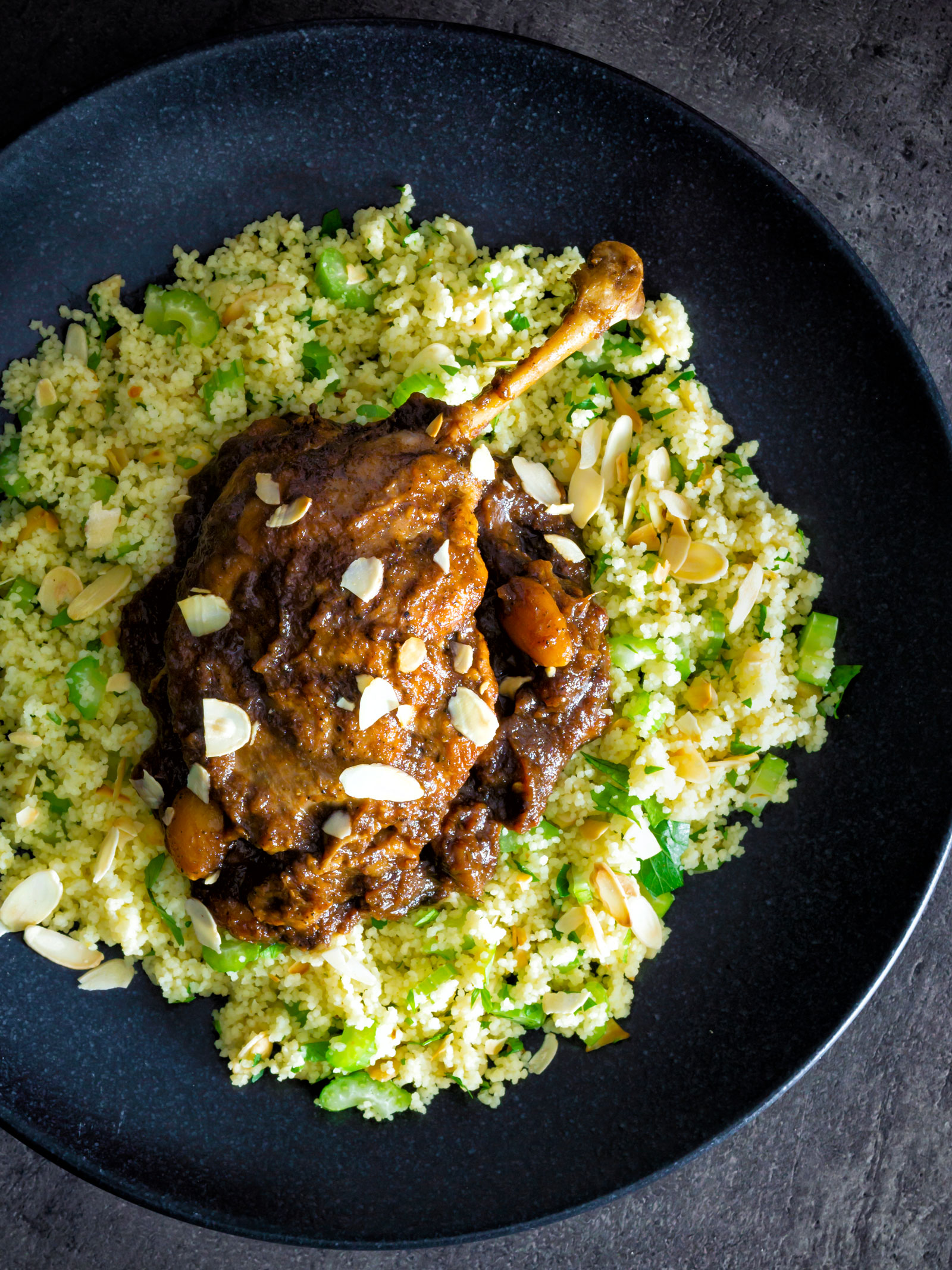 Overhead tamarind duck leg with a date and almond sauce served with couscous.